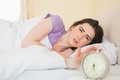 Irritated girl waking up in her bed by an alarm Royalty Free Stock Image