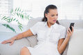 Irritated woman in white dress looking at her smartphone Royalty Free Stock Photo