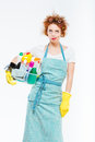 Irritated woman in yellow gloves holding box with cleansers Royalty Free Stock Photo