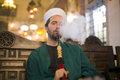 islamic man with traditional dress smoking shisha, drinking tea Royalty Free Stock Photo