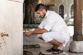 Islamic religious rite ceremony of ablution hand washing muslim man preparing to take in mosque Royalty Free Stock Photography