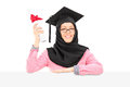 Islamic student with mortarboard and veil holding diploma behind female blank panel isolated on white background Royalty Free Stock Photo