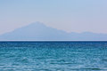 Island land in distance and mountain seen from sea level Stock Photography