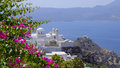 Island of milos greece bougainvillea in bloom on the in the cyclades with a whitewashed greek orthodox church and houses on a Royalty Free Stock Image