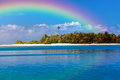 Island with palm trees and a rainbow over it Stock Photos