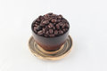 Isolate coffee beans in dark brown cup with small dish on white Royalty Free Stock Photo