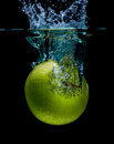Isolated apple splashing green with water on a black background Royalty Free Stock Photos
