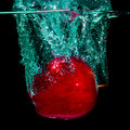 Isolated apple splashing red with water on a black background Stock Photos