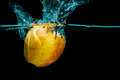 Isolated apple splashing yellow with water on a black background Stock Image
