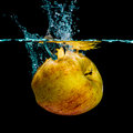 Isolated apple splashing yellow with water on a black background Royalty Free Stock Photo