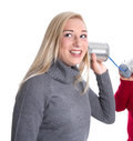 Isolated blond smiling young girl with a grey winter pullover on white background on the telephone curious Royalty Free Stock Photo