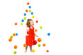 Isolated cute preschooler girl happy under falling colourful plastic balls on white Royalty Free Stock Image