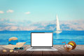 Isolated display of laptop on wooden table for mockup.  Sea, yacht and blue sky in background. Royalty Free Stock Photo