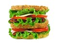 Isolated double decker sandwich large on a whole grain bread with ham tomato lettuce and cheese Stock Images
