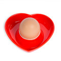 Isolated egg in a red heart-shaped eggcup Stock Photography
