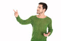 Isolated man in green pullover pointing and looking sideways to over white background text Stock Images