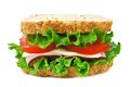 Isolated sandwich on a whole grain bread with ham tomato lettuce and cheese Stock Photography
