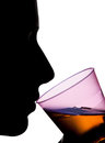 Isolated silhouette of a woman drinking orange liquid s face from transparent pink glass Royalty Free Stock Photos