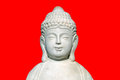 Isolated smiling buddha statue against red background Royalty Free Stock Images