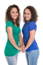 Isolated smiling young girls real twin siblings holding hands t together wearing blue and green shirt Stock Photography