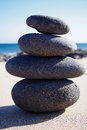 Isolated stacked zen stones near seashore pyramid at the seaside sunny day Royalty Free Stock Photo
