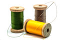 Isolated wooden spools of thread with a needle Royalty Free Stock Photo