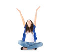 Isolated young woman with hands up sitting in crossed legs female trainee on the ground wiht over white background Royalty Free Stock Image