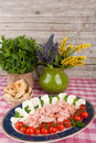 Italian appetizer table with appetizers plate consisting in mortadella mozzarella and cherry tomatoes Royalty Free Stock Images