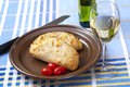 Italian bread and white wine two filled breads called calzone with tomatoes on a plate a glass of Royalty Free Stock Image