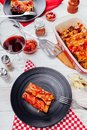 Italian cannelloni stuffed with minced meat and served with tomato sauce on black plates. Dinner for two Royalty Free Stock Photo