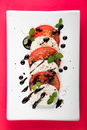 Italian Caprese salad with Mozzarella Tomato Oregano Black Pepper and Balsamic Vinegar on White Plate on Red Background Royalty Free Stock Photo