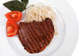 Italian cuisine grilled beef steak with pasta and tomatoes on basil leaf on plate isolated over white background Royalty Free Stock Images