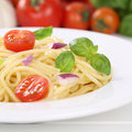 Italian cuisine spaghetti noodles pasta meal with tomatoes on pl food and basil plate Royalty Free Stock Photography