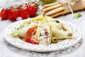 Italian cuisine: stuffed pasta shells and stack of breadsticks. Royalty Free Stock Photography
