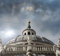 Italian dome detail of at cathedral with marble statues and cross on top with dramatic skyscape Stock Image