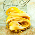 Italian fetuccine pasta closeup of coiled ribbons with an old wire kitchen strainer in the background Royalty Free Stock Photography