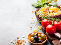 Italian food background with vine tomatoes, basil, spaghetti, olives Ingredients on stone table Copy space Royalty Free Stock Photo