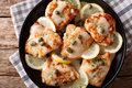 Italian food: chicken piccata with sauce, lemon and capers close