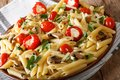 Italian food: penne pasta with mushrooms, cherry tomatoes, stuff Royalty Free Stock Photo