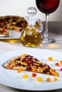Italian gourmet pizza accompanied by red wine and spices Royalty Free Stock Photo