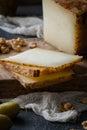 Italian hard cheese pecorino toscano sliced on wooden board with green olives and walnuts Royalty Free Stock Photo