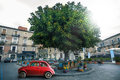 Italian old red car parked near a tree in a square in the city of catania in italy small subcompact with nobody inside it Stock Image