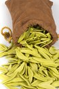 Italian pasta emptied from the bag with spinach Stock Photography