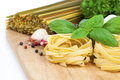 Italian pasta fettuccine nest with garlic and fresh basil leaves on wooden board Royalty Free Stock Photo