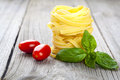 Italian pasta fettuccine nest with  tomatoes and fresh basil Royalty Free Stock Photo