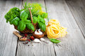 Italian pasta fettuccine nest with wicker basket green herbs Royalty Free Stock Photo