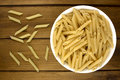 Italian pasta penne in plate on wooden background Royalty Free Stock Photo