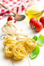 Italian pasta tagliatelle tomatoes and basil leaves on white table Royalty Free Stock Image