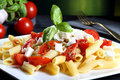 Italian pasta with tomatoes and mozzarella cheese white ceramic green background Stock Photos