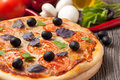Italian pizza margherita with tomatoes olives and basil on vintage rustic background Stock Photography